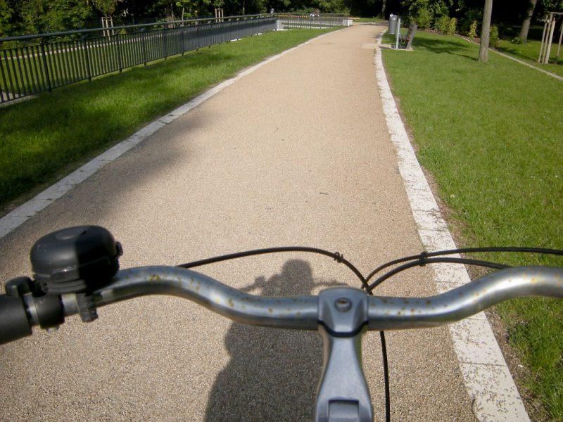Fahrradfahrt auf Weg, Wiese links und rechts des Weges, Doping, Clebuterol